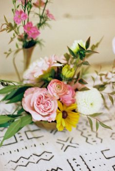 mixed flowers on mudcloth, photo by Amber Snow http://ruffledblog.com/austin-botanical-inspired-shoot #centerpieces #pink #yellow