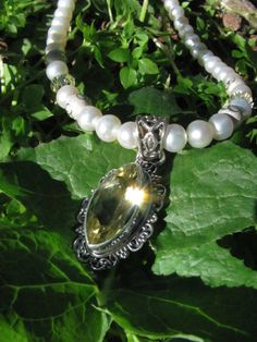 Grade A freshwater pearl necklace with sterling peridot pendant, Swarovski crystals, and silver intertwining ring beads