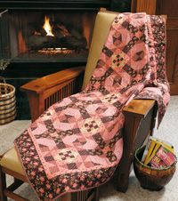 """Cherries Jubilee: Quilt designed and made by Dawn Stewart. Designer Dawn Stewart used a gorgeous palette of classic calicoes in deep browns and pinks to create this cozy quilt. These timeless prints were inspired by fabrics from 1882.  Size: 60"""" × 70""""  Blocks: 30 (10"""") blocks  FonsandPorter.com"""