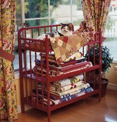 Old changing table turned into great quilt display - I like that it is red and also a kitty bed (maybe not on purpose).....love this!!!!