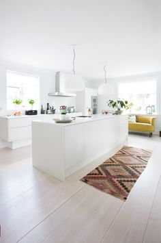 http://cococozy.com White kitchen, no upper cabinets, light wood floors.
