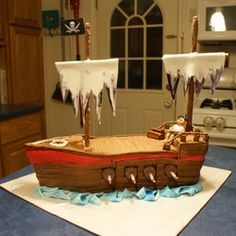 Pirate ship cake with maybe cotton candy sails, pretzel rod masts, pretzel square railings. Oreo portholes. Cannons? Swords from bar. Taffy waves?