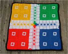 A crocheted version of a British board game called Ludo.