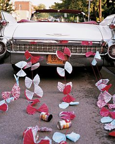 A 1959 Cadillac convertible decorated with paper accordion fans.
