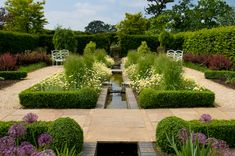 A formal water garden with fountain and rill, bordered by gravel and flagstone paths and boxwood framed beds of daisies, grasses and allium, Merriments, England