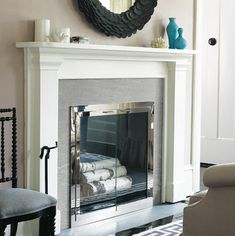 A slate surround and glass doors update a tired fireplace. | Photo: David Price | thisoldhouse.com