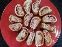 """Reuben Rolls - 1/3 Cup mayonnaise 1 Tbsp Dijon-style mustard ½ tsp caraway seeds 1 Cp cooked corned beef, finely chopped 1 Cp shredded Swiss cheese 1 Cp sauerkraut rinsed drained & patted  1 10oz pkg thin refrigerated pizza crust dough  Combine ingredients in a bowl. Unroll pizza dough onto large ungreased cookie sheet. Cut dough lengthwise in 1/2. Spoon 1/2 of the filling onto ea piece, spreading to within 1"""" of edges. From long side, roll ea jelly-roll style; pinch edges. Bake 425F for 10 mins"""