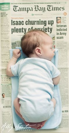 baby on a newspaper from the day he or she was born  Cool Idea just to keep a paper from the day the baby is born. Would be cool to look back on.