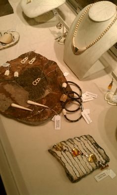 Fossil mammoth bone and amber jewelry on a crinoid fossil and a mammoth tooth slice at @hmns.
