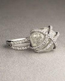 A rough diamond ring hugged by cut diamonds