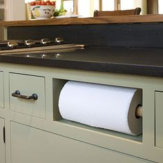 Replace faux drawer under sink with paper towel roll.  Utilizing useless space and getting the miscellaneous off the counter is always a good idea... no matter how good looking the towel holder is!  Love it!