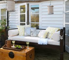 Make over a porch with a few items (day bed, potted plants, Chinese lanterns) that will make the space comfortable and stylish.
