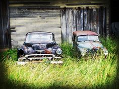 Abandoned cars by an old barn