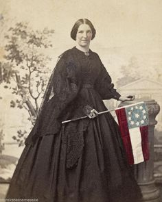 8 by 10 Photo Print Civil War Smiling Woman Holding 11 Star Confederate Flag- much of this ladies attire gives the impression of being of mourning, question is, whom is she mourning.