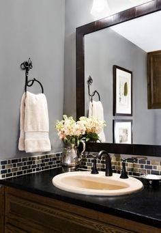 The glass tile backsplash and black color accents of the countertop and mirror look fine with the gray paint... http://www.bathroom-paint.net/bathroom-paint-color.php