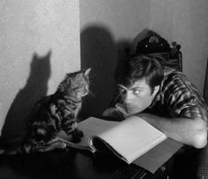 Oliver Reed and his feline companion read.