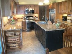 honey oak cabinets updated with black cabinets and new countertops. This would work in my home.