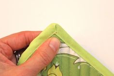 """Sewing Tutorial: How to Sew Bias Tape, Part II: Corner Edition, by Maggie on her blog, """"Smashed Peas and Carrots"""" (11 Jan. 2011). Here's a clear tutorial with lots of pictures showing how to sew mitered corners when applying bias tape edging to a project."""
