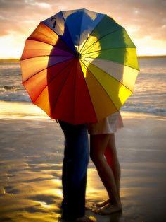 Hidden kiss under rainbow umbrella.