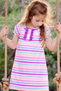 Sweet Shirred Peasant Dress Tutorial - You can choose any fabric to make sure your little girl loves her new dress. Pair it with shorts or leggings for a perfect back to school outfit.