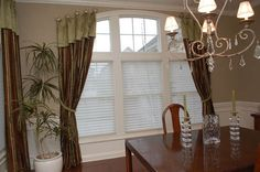 Drapery panels mounted with medallions over an arched window.