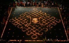 Onlookers stand beside lit earthen lamps during celebrations on the eve of the Hindu festival of Diwali in the northern Indian city of Chandigarh October 16, 2009. (REUTERS/Ajay Verma) #