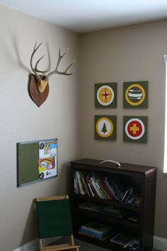 Outdoor nature hiking camping theme boys bedroom. Deer antler animal mount. Painted bulletin board book case and reading chair.
