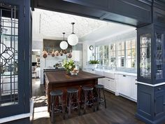Custom navy display cases frame out the entrance to this Old-World-inspired kitchen by Candelaria Design. Painting the woodwork in this dark hue, rather than standard high-gloss white, draws attention to the cases themselves and makes the white kitchen beyond feel even brighter by comparison.