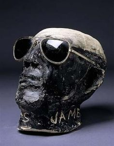"""Black Skull with Sunglasses    ca. 1970 James """"Son"""" Thomas Born: Eden, Mississippi 1926 Died: Greenville, Mississippi 1993 unfired clay, foil, wax, metal, and plastic sunglasses overall: 7 1/2 x 9 1/2 x 6 1/2 in."""