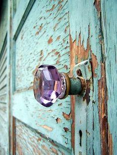 Lavender doorknob on a weathered turquoise door