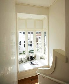 cozy sun-filled window seat at the bottom of the stairs