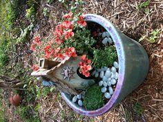 Fairy garden in a pot.  The stones glow in the dark!