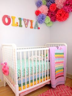 This is an adorable crib and bedding. I also LOVE the little corner poms.