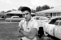 Elvis in the front yard of his home at 1034 Audubon Drive in May 1956. When this photo was taken, Elvis had just returned from touring; the band's instruments were still packed on the roof of his car. His famous pink Cadillac can be seen over his right shoulder.  v