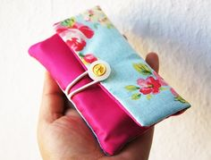 A beautiful handmade cellphone pouch for protecting your phone or iPod. It is made from a very nice and lovely fabric with vintage gold button on top.