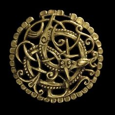 """Gilded bronze Anglo-Scandinavian brooch, 11th century AD.Found in Pitney, Somerset, England. """"An entwined animal and snake in combat…. The design, with its plant-like tendrils and ribbon animals, is an English version of the final phase of Viking art, the Urnes Style. However, the delicate beading which picks out the main animal, and the scalloped border of the brooch are both Anglo-Saxon features…."""""""
