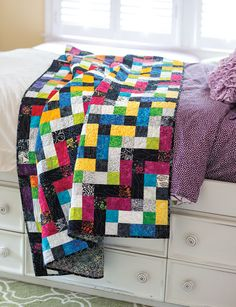 """Chain Link is a batik quilt that features only squares and triangles in a simple block pattern. """"Quilting should be fun,"""" says designer Nancy Mahoney, and what's more fun than working with bright batiks? Video quilting tutorial available! Find this quilt in Quilting Quickly Fall '14."""