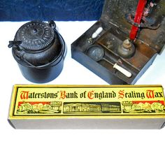 Sealing wax from England. The iron pot is for melting wax. It has an insert of iron inside so it is often confused with an inkwell. The box on the right is also for melting wax to seal a letter. It comes equipped with sealing wax, oil lamp, ivory small seal, and an ivory handled ladle that sits nicely on top of the flame. It has a slot where wax can be poured directly on the letter without getting hot wax on your hand._Judith Walker's Collection