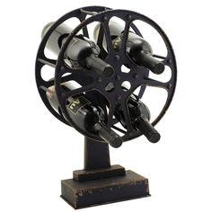 Movie Reel Wine Rack for $58.00 from WineRacks.com  It's common to pair wines with food, but why stop there?  Pair your favorite bottle with your favorite film and display your wines in this fun metal Movie Reel wine rack. A unique, fun and functional design, weighted base for sturdy storage.   Holds 4 standard size bottles