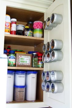 Spice cabinet organization. Spice canisters stay on the door with the use of magnetic paint.