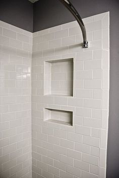 White tile shower ideas;  white subway tile-shower niche with bullnose edge tile used in lieu of bullnose strip pieces. Also subway tiles turned vertical on edges of shower.