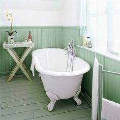 To achieve a cohesive look in this serene cottage-style bath, the pine floorboards, baseboards, and wainscoting are painted a similar sage-green. | Photo: David Palmer/IPC Images