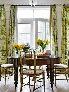 dining room with bamboo chairs tile floor round table, green and white curtains