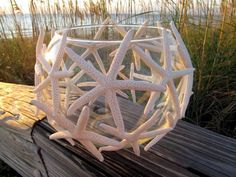 White pencil starfish placed in rings around a clear glass bowl