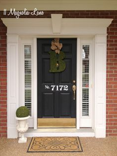 Moss, burlap, and black and white pillows are used on the spring front porch at 11 Magnolia Lane. Tutorials for the moss-covered initial, the moss sphere, and the house number pillow slipcovers are all available on the site.