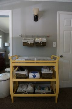 Smart use of a small space by using a towel bar and two baskets to hang diaper supplies! #nursery #organization