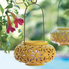 """FLORAL OASIS HANGING LANTERN  Item #:P91308Pierced floral lantern lends a tropical, exotic touch to your outdoor settings. For use with a GloLite by PartyLite™ Jar or Escential Jar, tealights or large tealights, all sold separately. Weather-resistant resin with wire handle. Some simple assembly. 13 1/4"""" (34 cm) h, 8 3/4"""" (22 cm) diam."""