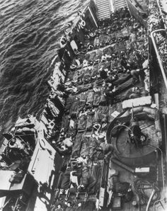 """Row upon row of stretchers cover the decks of a Coast Guard LCT bringing out wounded from France. These American and British soldiers fell somewhere between the beachhead and Cherbourg as Nazi defenders sought a high price in casualties for every yard they yielded. The wounded are being transferred to a Coast Guard assault transport which will carry them back to England for hospitalization."" June 1944. (US National Archives)"