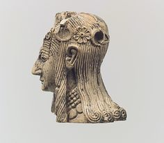 Assyrian female head with rosette diadems. Found in Nimrud, 8th century BCE.    At the Metropolitan Museum of Art in New York.