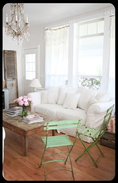 Love this living room! So light and airy. The green bistro chairs make me drool! I think I would do the sofa in a pastel or light neutral color since white can be too difficult to keep clean and bright in a lived in room.